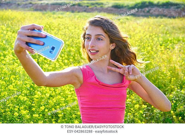 Teen girl serfie video photo in spring meadow gesturing
