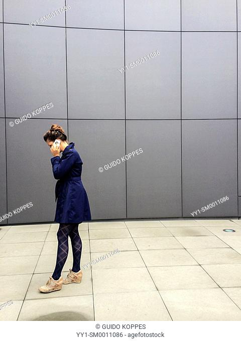 Breda, Netherlands. Young, attractive woman having a conversation through her smart phone, while walking up and down a courtyard