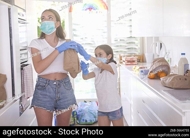 kid helps her mom in the kitchen during pandemic
