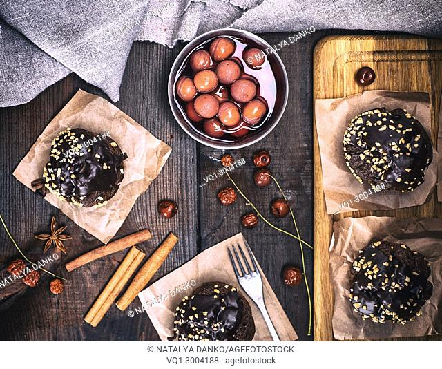 chocolate muffins with a cherry on a brown wooden table, top view, vintage toning