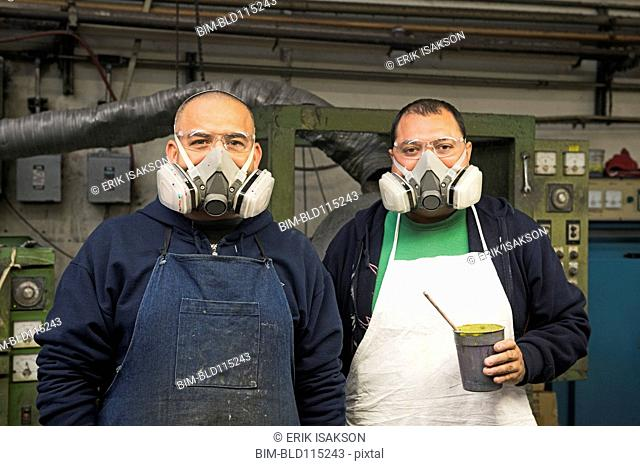 Hispanic workers wearing gas masks in textile factory