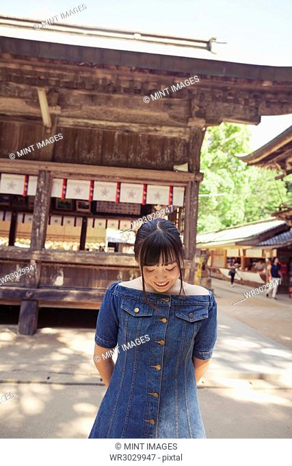 Young woman wearing blue dress standing at Shinto Sakurai Shrine, Fukuoka, Japan