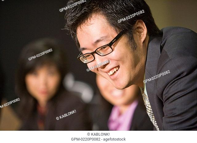 Three Asian businesspeople discussing in boardroom, focus on man in foreground