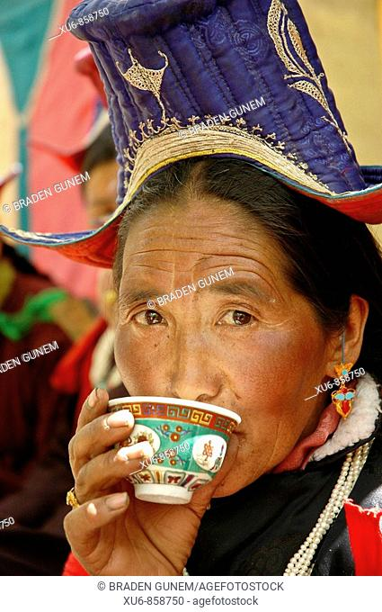 Ladakhi woman drinking chhang beer Alchi, Ladakh, India