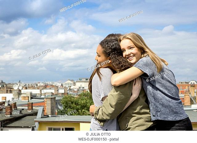 Three happy teenage girls hugging each other on roof top