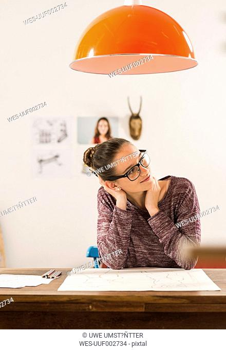 Smiling young woman with drawing at home
