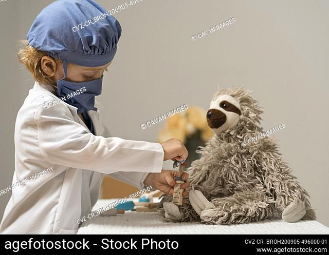 young child in medical PPE examines a plush toy sloth and administers a shot with syringe