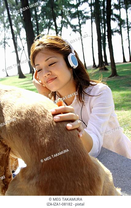 Close-up of a young woman wearing headphones and stroking a dog