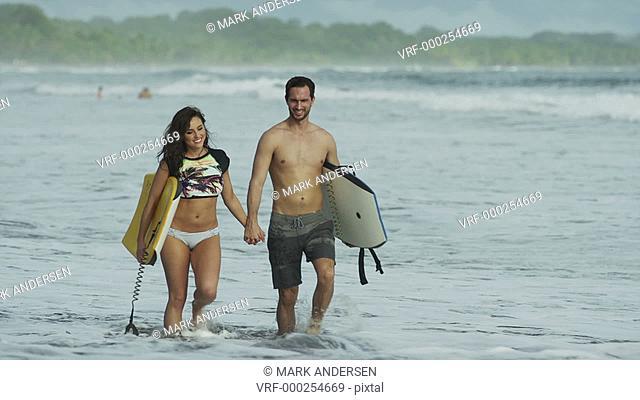Medium tracking shot of couple walking in ocean waves / Esterillos, Puntarenas, Costa Rica