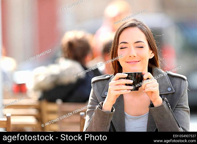 Front view portrait of a satisfied woman smelling a cup of coffee on a restaurant terrace