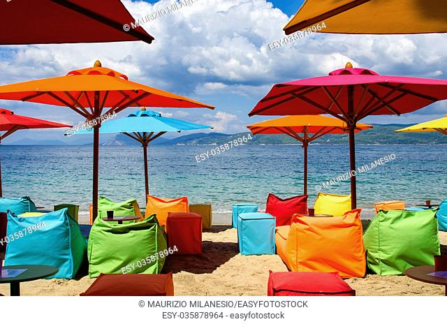 Modern beach equipped with umbrellas, and multicolored inflatable deckchairs for trendy tourists, Skiathos Greece, at the bottom the sea and a cloudy sky