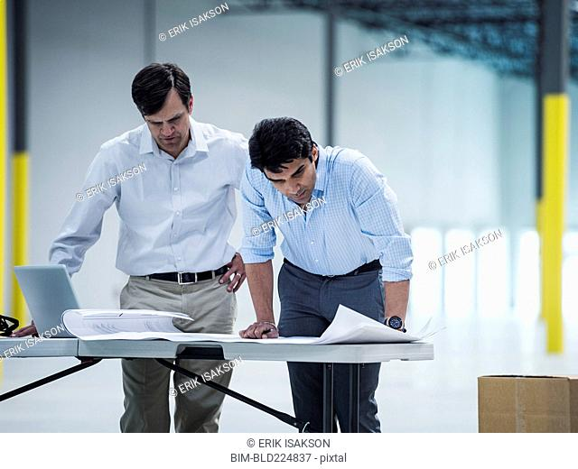 Architects using laptop and blueprint in warehouse