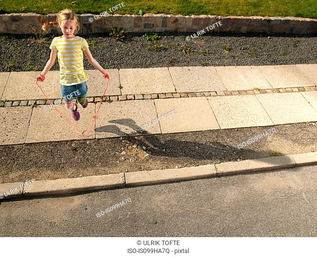 Young girl skipping on sidewalk