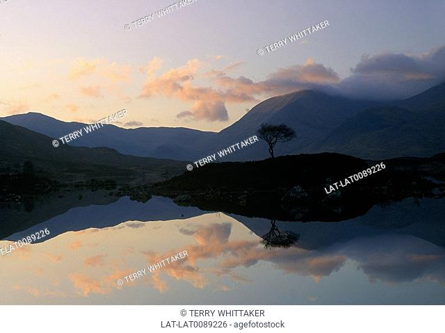 Sunrise,sunset. Silhouette of hills. Pink cloud,light in sky. Reflection in lake,loch water