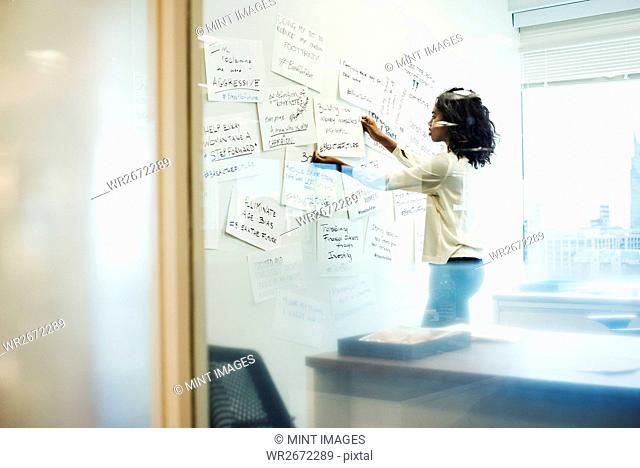 A woman standing in an office arranging pieces of paper pinned on a whiteboard