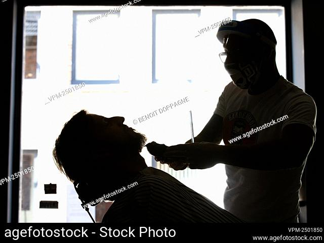 Illustration picture shows a hairdresser wearing a mouth mask and facial protection as he performs a demonstration haircut on a friend belonging to his 'bubble...