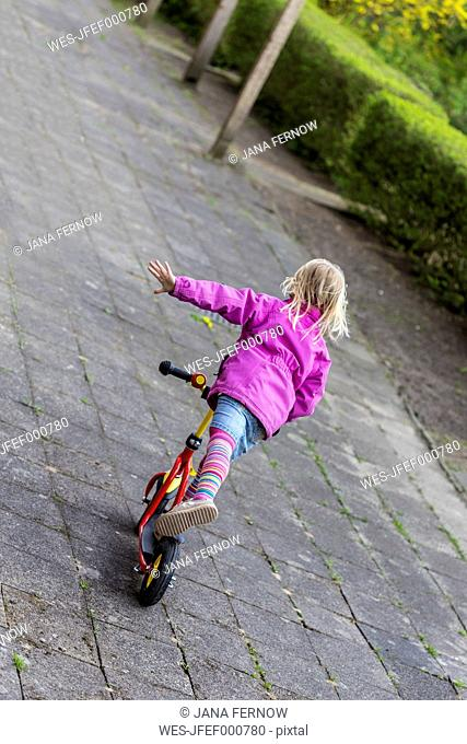 Back view of little girl balancing on her scooter