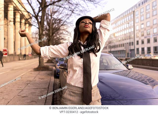 stylish woman dancing with arms in evening sunlight at street, wearing retro outfit, business look, African Angolan descent, in city Munich, Germany