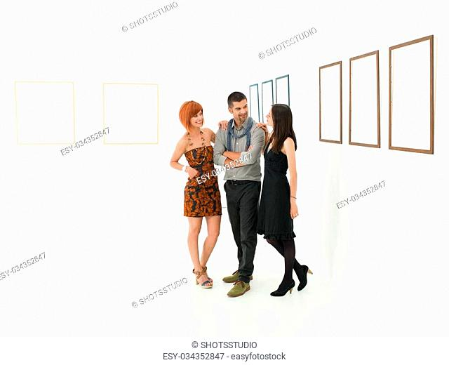 young beautiful women holding her hands on a man's shoulders and smiling in a room with empty frames displayed on white walls