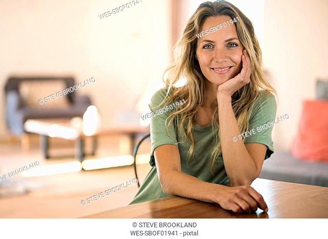 Portrait of smiling blond woman at home resting her head on the hand