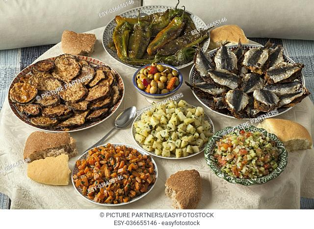 Moroccan meal with a variety of dishes with fresh cooked sardines, vegetables and bread