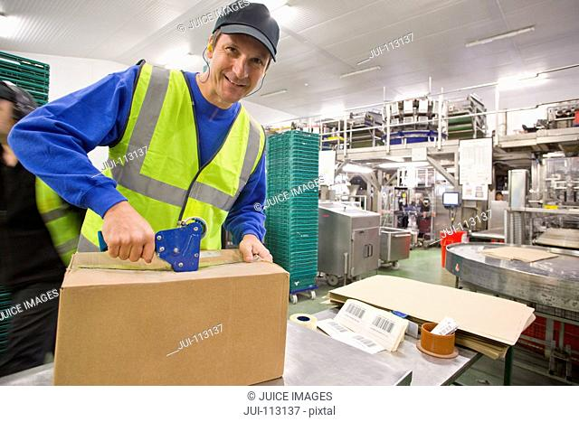 Portrait smiling worker taping box in food processing plant