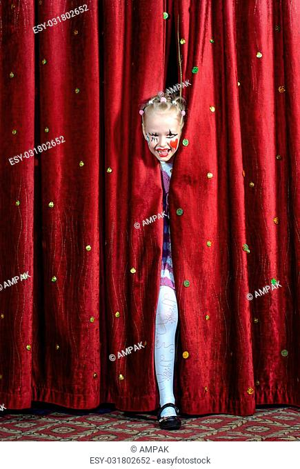 Little girl performing in a pantomime peeking through the curtains on stage in her makeup with a big smile as she waits to make her entrance