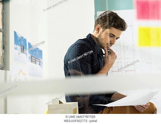 Young man in office reviewing documents