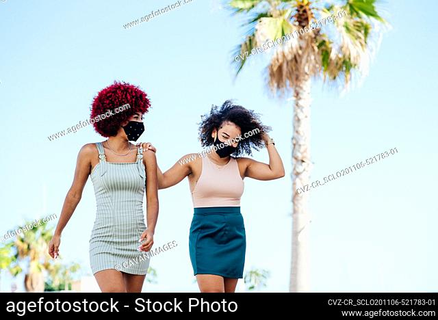 Two latin women with protection mask walking along a promenade
