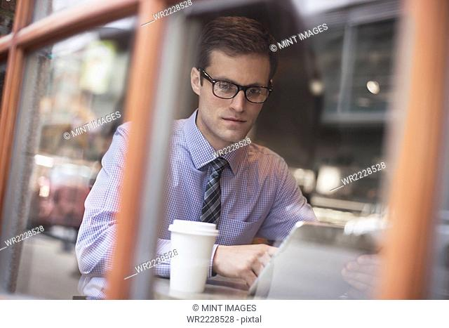 A working day. Businessman sitting in a cafe, using laptop, having coffee