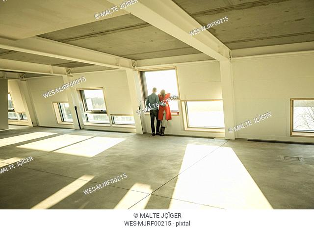 Couple looking out of window of their new home