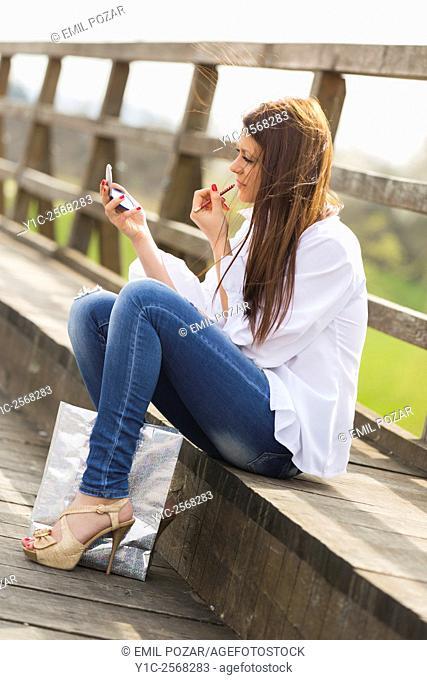 Fixing make-up outdoors girl teenager in denim pants