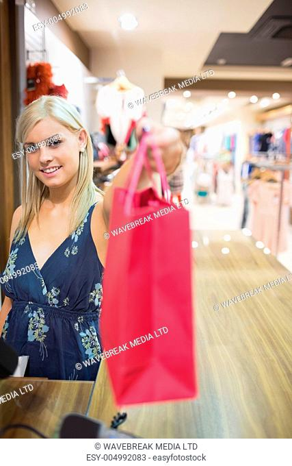 Smiling woman passing shopping bag over counter in clothes store