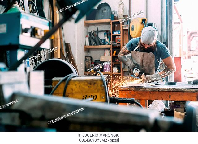 Axe maker using steel grinder in workshop