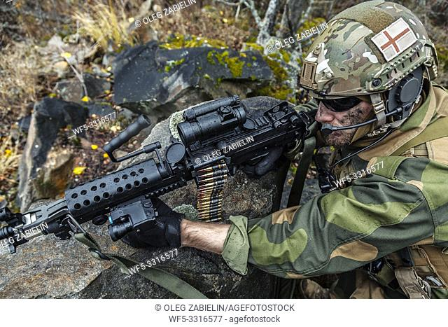 Norwegian Rapid reaction special forces FSK soldier firing among the rocks. High angle foreshortening diagonal view