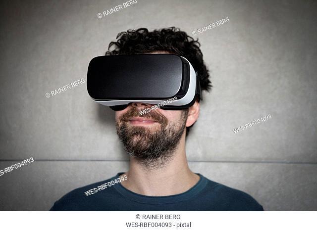 Smiling man wearing Virtual Reality Glasses