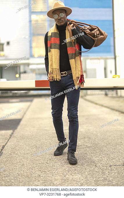 classy man with stylish casual men's fashion outfit, at barrier at industrial area in Munich, Germany