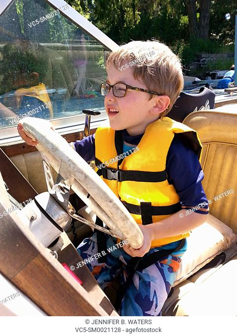 A boy pretending to drive a boat while it is parked at the dock at the Pend Oreille River, Idaho, USA