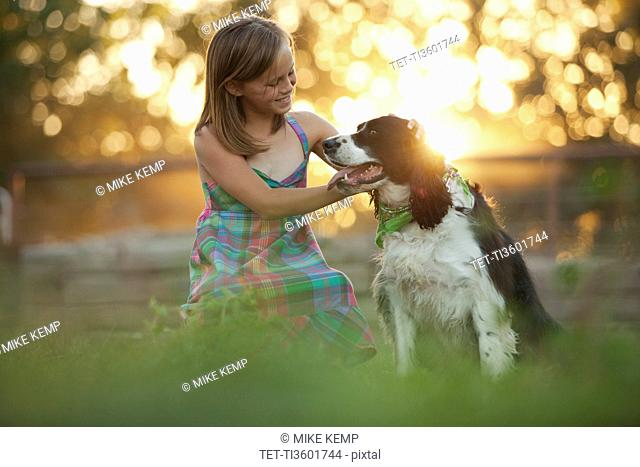 Girl 8-9 stroking dog in field
