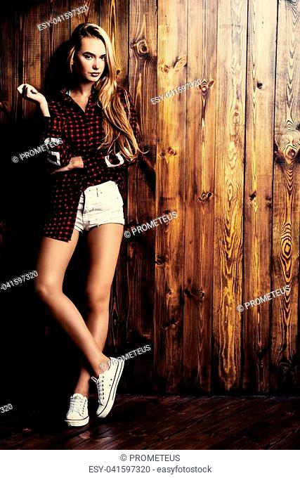 Full length portrait of a pretty blonde girl over wooden background. Beauty, youth fashion