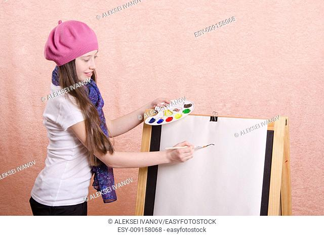 Twelve year old girl draws a picture on the easel