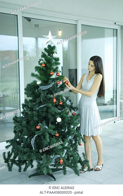 Woman putting decorations on Christmas tree, full length