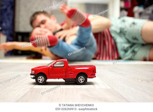 Red toy car staying on the floor, father and son playing at background