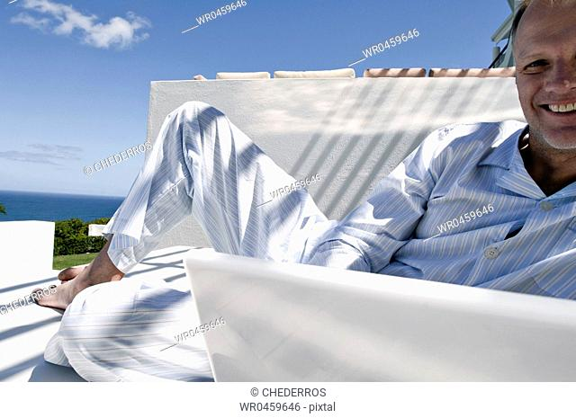 Portrait of a mature man using a laptop on the bed and smiling