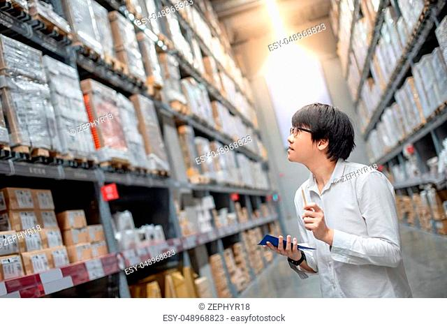 Young Asian man checking the shopping list and looking for product in cardboard box in warehouse wholesale, shopping warehousing concept