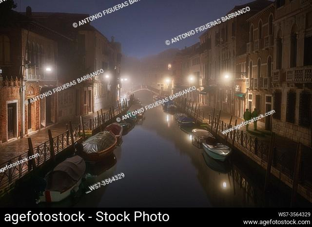 Foggy sunrise on a lonely canal in Venice
