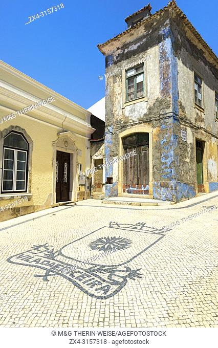 Coats of arm of Ericeira city on cobblestones in front of an old house, Ericeira, Lisbon Coast, Portugal