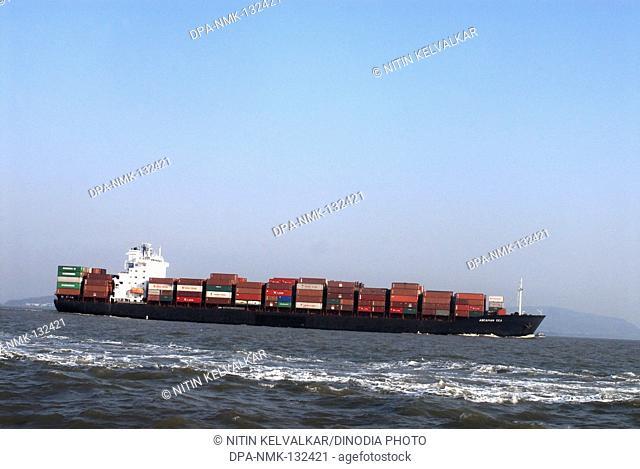 Fast moving huge cargo Ship fully loaded with container in Arabian sea near Gateway of India ; Mumbai Bombay ; Maharashtra ; India