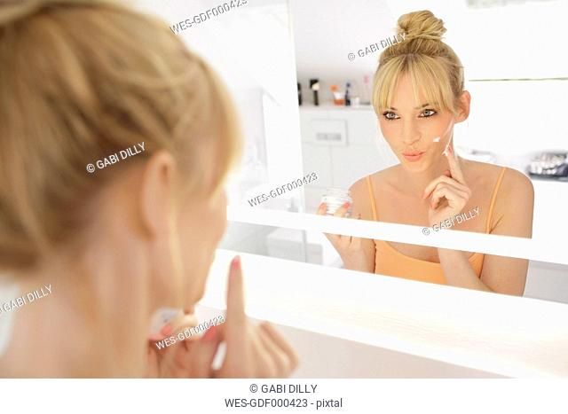Woman looking at her mirror image while applying face cream