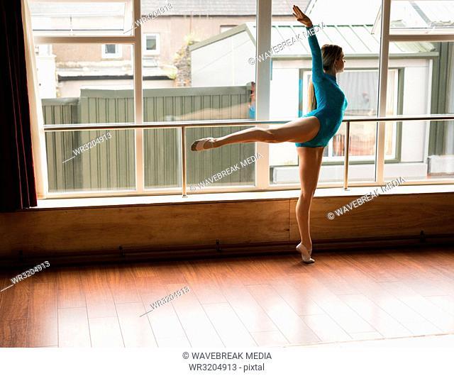 Ballerina practice arabesque ballet position in studio